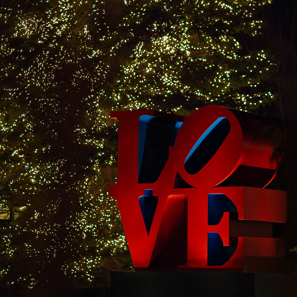 Love sculpture by Robert Indiana in front of a christmas tree in a hotel garden in Zurich.